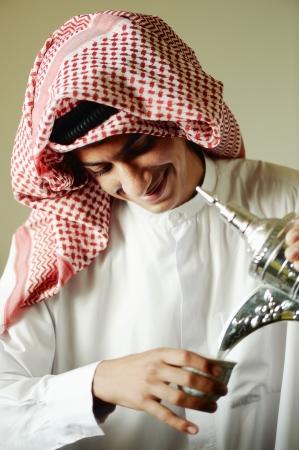 Hombre árabe joven verter un café tradicional Foto de archivo