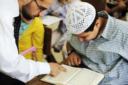 Arabic middle eastern students at school reading Koran photo