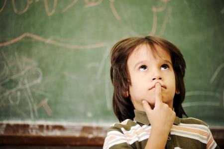 niños pensando: Los niños en el aula de la escuela Foto de archivo