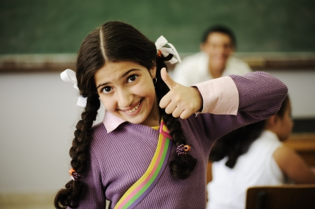 Cute little girl at school with thumb up photo