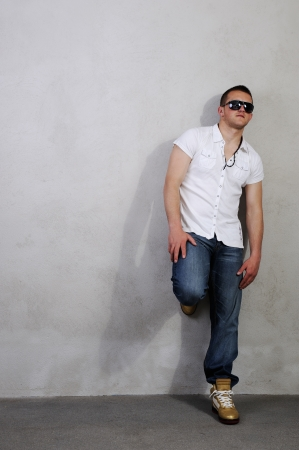 tall glass: Man in dark glasses leaning on the wall Stock Photo