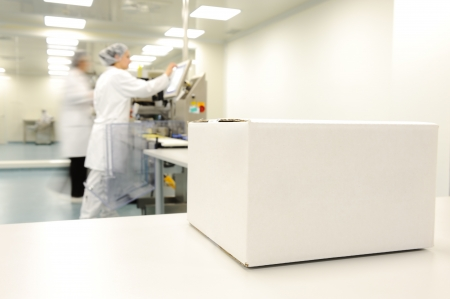 Crate in front of medical staff in modern factory Stock Photo