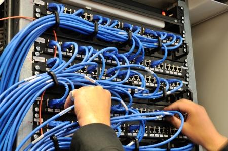 fiber cable: Man verbinding netwerkkabels aan schakelaars Stockfoto