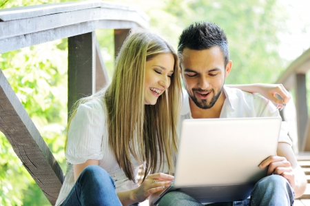 Two students sitting in park using laptop photo