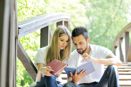 Beautiful couple reading book outdoors photo