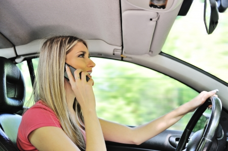 Hot sexy woman talking on a mobile phone while driving a car photo