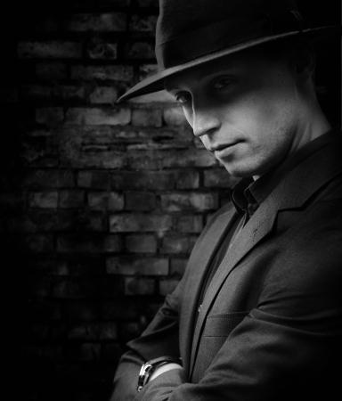Man with hat standing against dark brickwall background photo