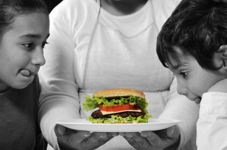 Mother giving a burger to son and daughter photo