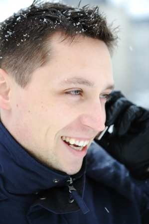 Young male adult speaking on phone at winter snow time photo
