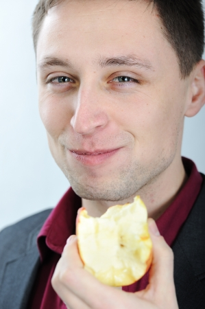 Young man eating apple photo