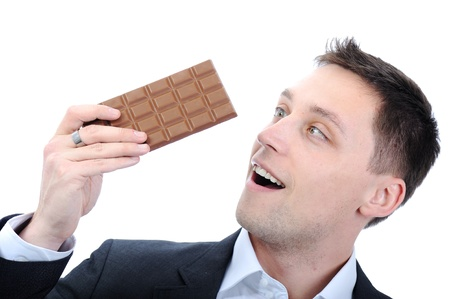 Young business man eating chocolate photo