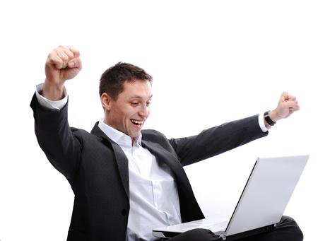 Eccitato uomo utilizzando il computer portatile con le braccia in aria