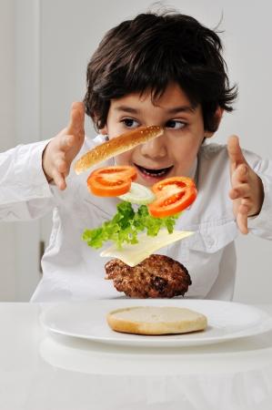 zero gravity: Little boy con ingredienti hamburger in mano