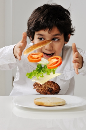 mastery: Little boy with hamburger ingredients in hands