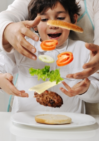 Mother and son making burger at kitchen photo