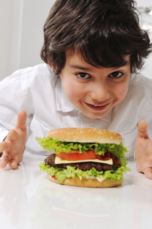 Cute little boy with burger photo
