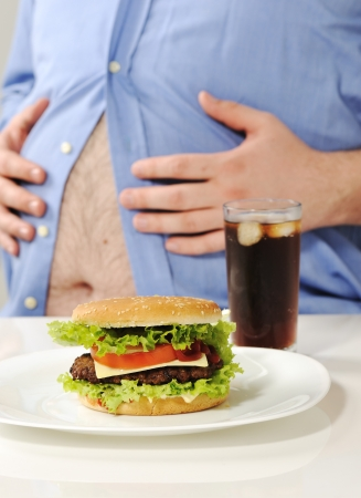 unhealthy lifestyle: Fat stomach with burger and cola Stock Photo