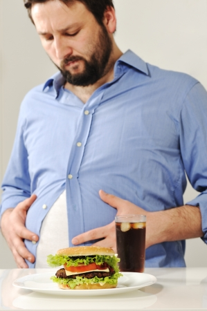 spijsvertering: Fat man zorgen over fast junk food Stockfoto