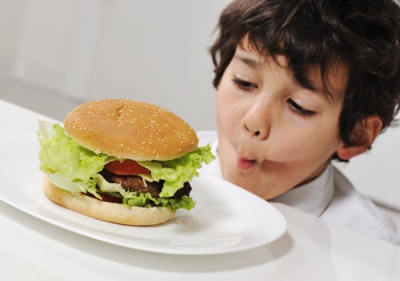 Kid on temptation with delicious hamburger photo