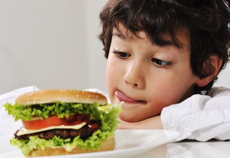 Boy on temptation with burger photo
