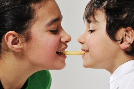 food fight: Sister and brother eating french fries