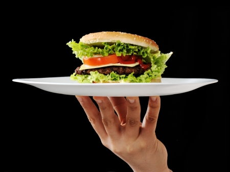 Hamburger in hand on plate photo