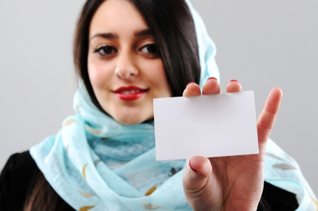 east: Arabic woman holding visit card with copy space