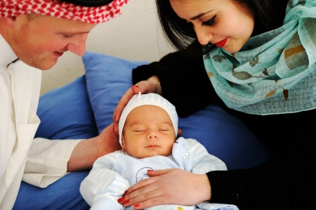 muslim baby girl: Arabic Mother and Father with baby at home Stock Photo