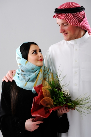 Arabic couple, wife and husband holding boquet of flowers photo