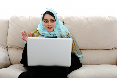 arab girl: Young woman with laptop on couch Stock Photo