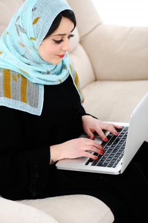 fille arabe: Jeune femme avec un ordinateur portable sur le canapé