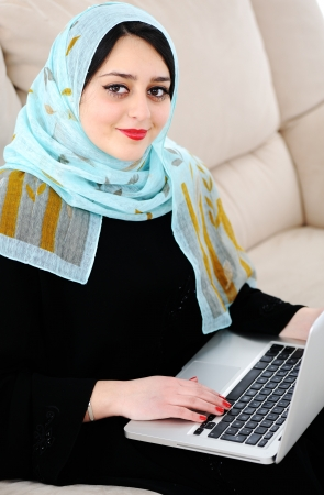 Young woman with laptop on couch photo