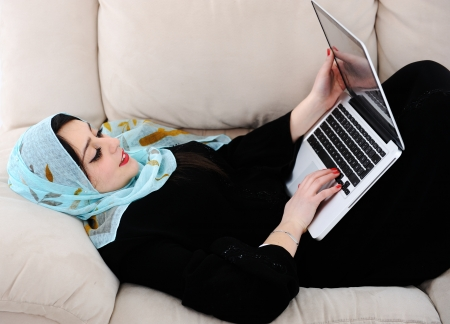 Young woman with laptop lying on couch photo