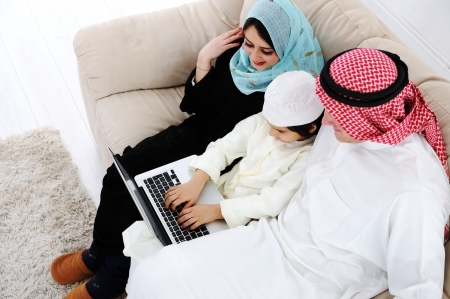 Parents and little boy at home with laptop computer photo