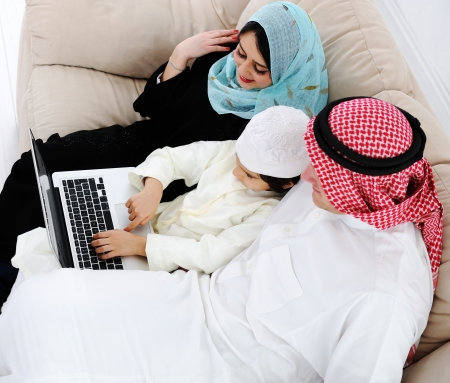 learning arabic: Parents and little boy at home with laptop computer
