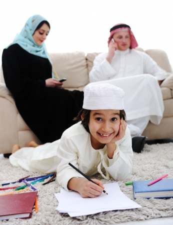 Happy kid working on homework at home with his family photo