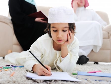 learning arabic: Happy kid working on homework at home with his family