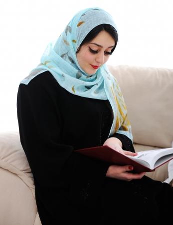 arabic woman: Muslim arabic woman reading book on sofa