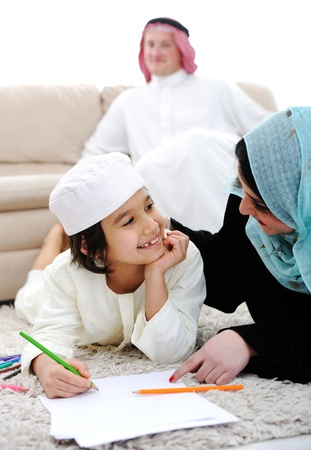 middle eastern families: Happy kid working on homework at home with his family