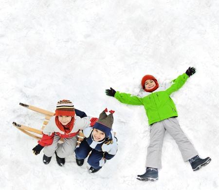 snow ground: Happy kid lies on snow ground