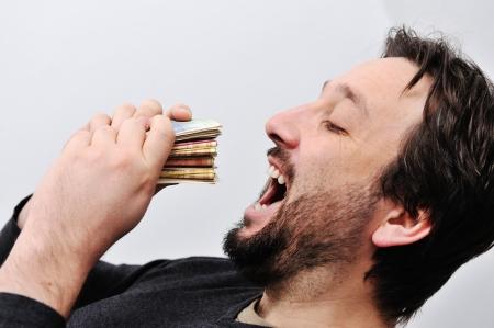 avid: Man eating money Stock Photo