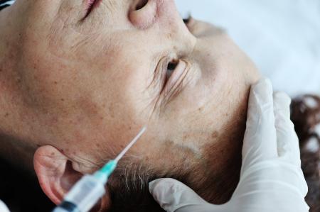 surgical needle: Elderly woman getting Botox injection procedure