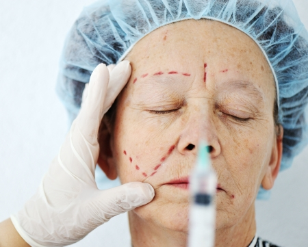 Elderly woman getting Botox injection surgery operation photo