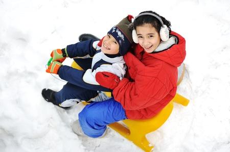 Kids sliding sledge in the snow Stock Photo - 16624836