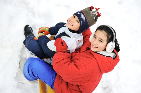 Kids sliding sledge in the snow Stock Photo - 16625009