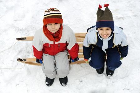 Kids sliding sledge in the snow Stock Photo - 16625105