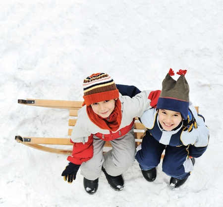 Kids sliding sledge in the snow sitting photo