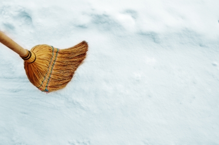 Broom broomstick on snow with copy space photo