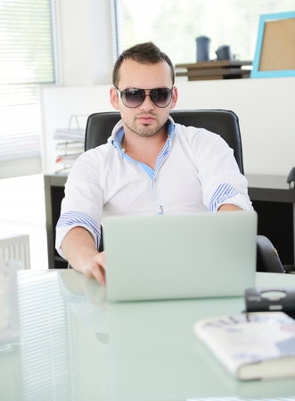 Young business man sitting and resting at modern office photo
