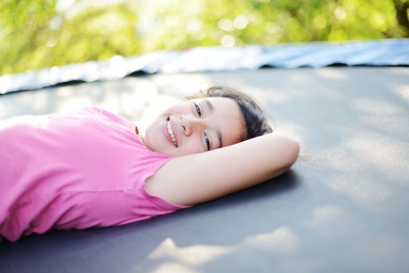 preteen: Portrait of a smiling little girl lying on green grass